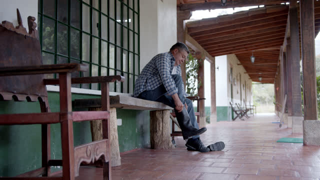 latin american farmer getting ready to work in the field putting on his rubber boots - colombia stock videos & royalty-free footage