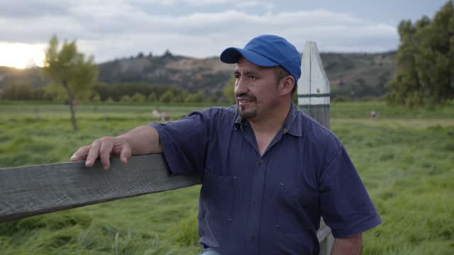 lateinamerikanischer bauer lehnt sich an holzzaun und schaut weg auf das landwirtschaftliche feld - latin american and hispanic ethnicity stock-videos und b-roll-filmmaterial