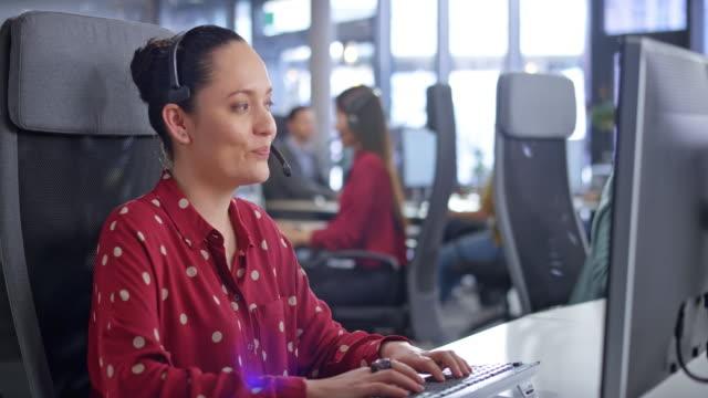 vídeos y material grabado en eventos de stock de ds latin american agente de centro de llamadas que proporciona servicio al cliente en su estación de trabajo en una oficina moderna - call center latin