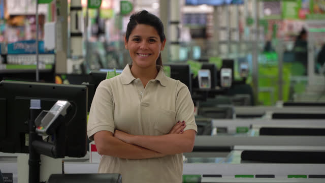 latin american female cashier at a supermarket smiling at camera while crossing arms - shop assistant stock videos & royalty-free footage