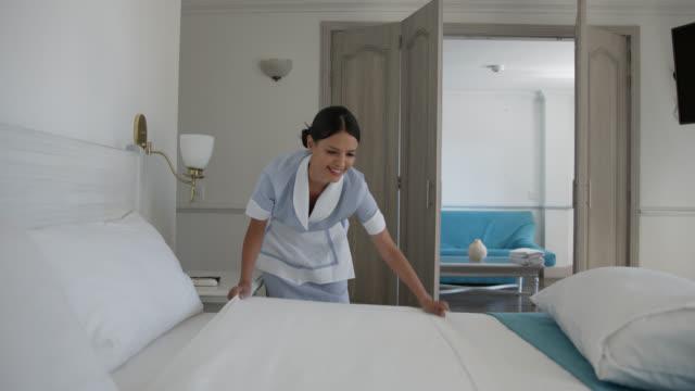 stockvideo's en b-roll-footage met latijns-amerikaanse vrouwelijke reinigingsdienst die het bed bij een hotel het glimlachen doet - dienstverlener