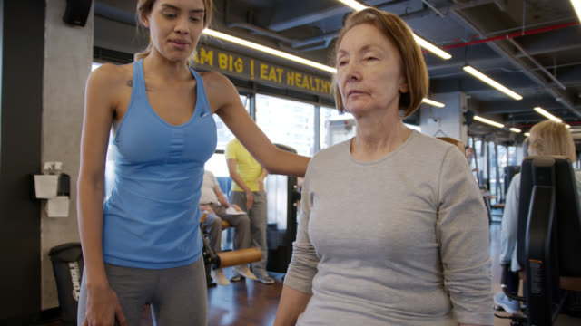 latin american female coach helping senior woman working out her legs on machine - active seniors stock videos & royalty-free footage