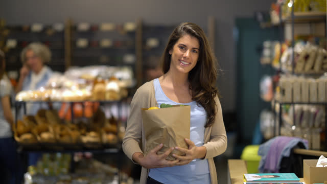 latin american female customer at a grocery market shopping walking up to the camera looking at it smiling - paper bag stock videos & royalty-free footage