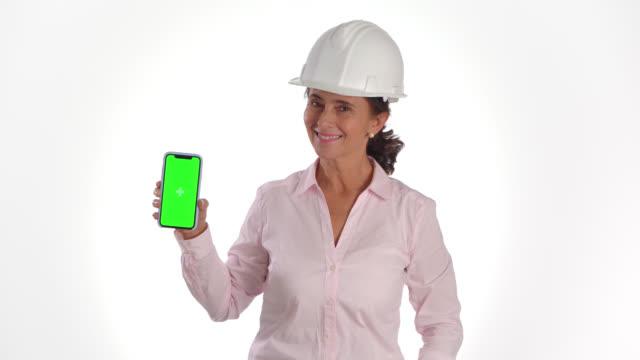 ingegnere latino-americano in possesso di uno smartphone che mostra lo schermo che guarda la fotocamera sorridente indossando un casco di sicurezza - mostrare video stock e b–roll