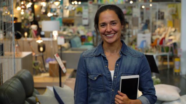vídeos de stock e filmes b-roll de latin american female interior designer at a furniture store holding a tablet while smiling at camera - interiores em exposição