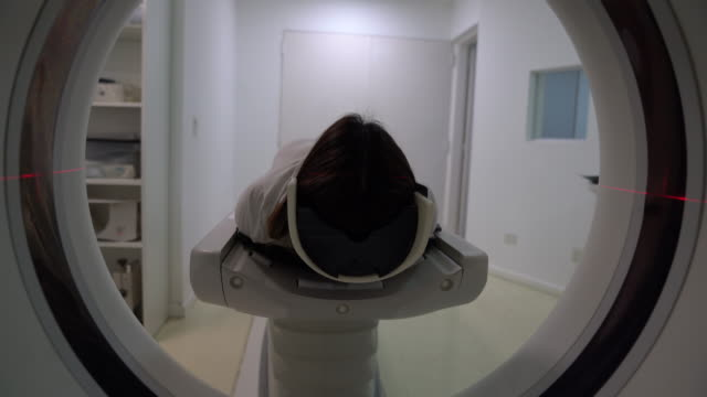 latin american female patient lying down on cat scan machine ready for the procedure - diagnostic medical tool stock videos & royalty-free footage