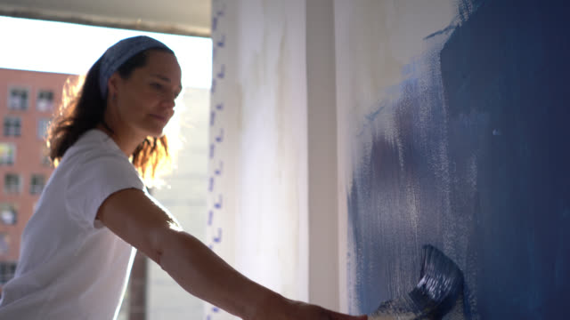 latin american focused woman painting a wall with a blue paint looking very focused - painting stock videos & royalty-free footage