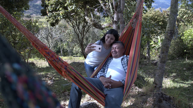 latin american girl taking a selfie with her grandfather while he is relaxing on a hammock at their country house - colombia stock videos & royalty-free footage