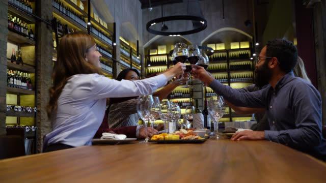 vidéos et rushes de groupe latino-américain d'amis à une dégustation de vin faisant un toast tous regardant très heureux - goûter