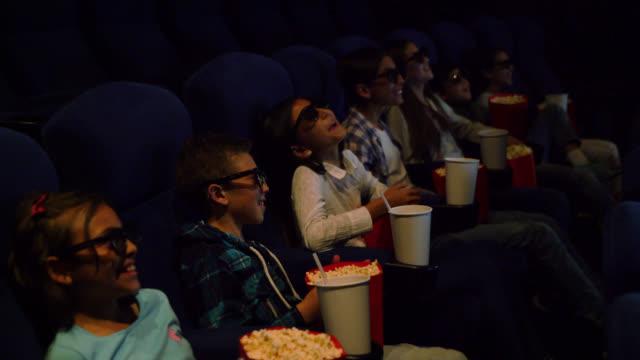 vídeos de stock, filmes e b-roll de grupo latino-americano de miúdos no cinema que presta atenção a um filme do comedy 3d ao apreciar petiscos - óculos de terceira dimensão
