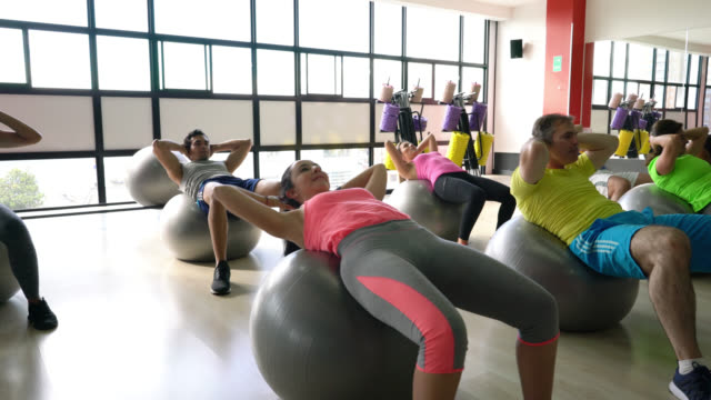 latin american group of people at class in the gym working out their abs on exercise balls - pallone per fitness video stock e b–roll