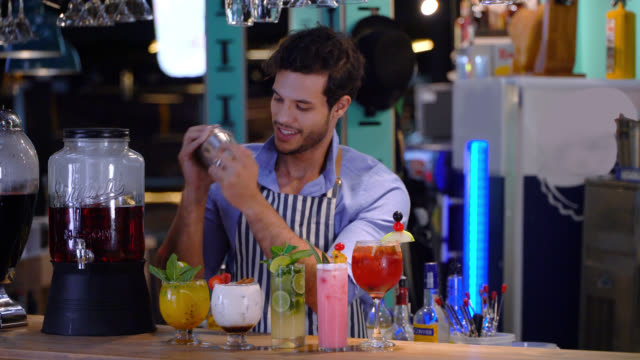 vídeos de stock, filmes e b-roll de bartender bonito latino-americano que prepara cocktails que sorriem muito feliz - barman