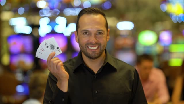 latin american handsome casino dealer holding cards while looking at camera smiling - casino worker stock videos and b-roll footage