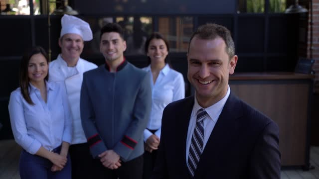 vídeos de stock e filmes b-roll de latin american handsome hotel manager looking at camera smiling and his team standing behind him smiling - hotel