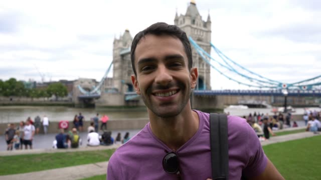 latin american handsome young student smiling at camera with the london bridge at the background - tower bridge stock videos & royalty-free footage
