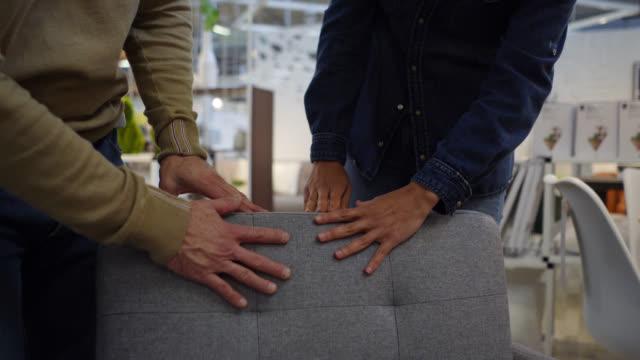 lateinamerikanische glücklich es paar blick auf verschiedene möbel in einem home-store sprechen und lachen - möbel stock-videos und b-roll-filmmaterial