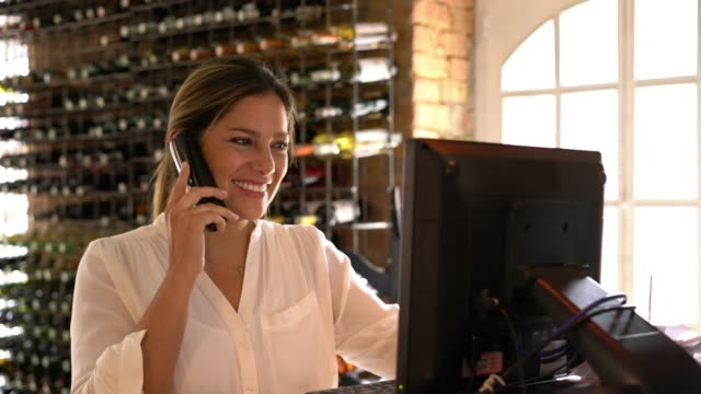 latin american hostess talking with a customer making a reservation while she adds it to the system very cheerfully - order stock videos & royalty-free footage