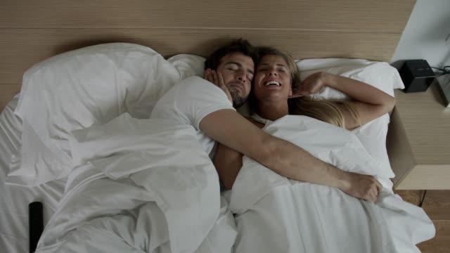 vídeos de stock, filmes e b-roll de casal amoroso latino-americano acordando e depois abraçando de volta juntos - deitando