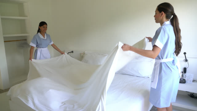 Latin american maids making the bed at a hotel