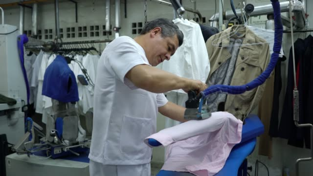 latin american male at a laundry service ironing a pink shirt and female ironing a jean - shirt stock videos & royalty-free footage