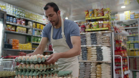 latin american male business owner of a small market arranging the egg display - vendor stock videos & royalty-free footage