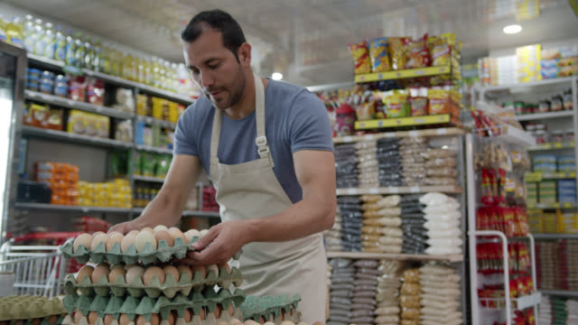 vídeos de stock e filmes b-roll de latin american male business owner of a small market arranging the egg display - trabalho no comércio