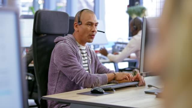 vídeos y material grabado en eventos de stock de agente latinoamericano de centro de llamadas para hombres responde a una llamada en su estación de trabajo - call center latin