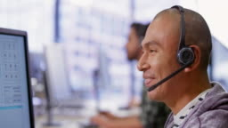 Latin American male call center agent talking with wireless headphones