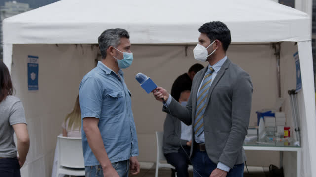 latin american male news reporter interviewing a patient waiting to get his vaccine at a covid-19 vaccinator stand - documentary footage stock videos & royalty-free footage