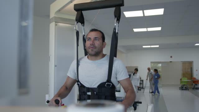 vídeos y material grabado en eventos de stock de paciente masculino latinoamericano durante la terapia física caminando con la ayuda de un robot de exoesqueleto - fisioterapia deportiva