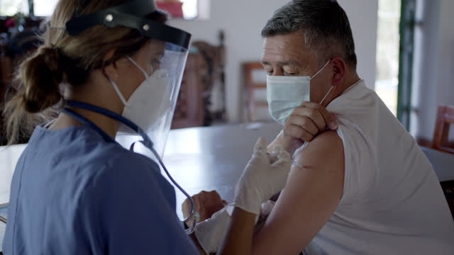 stockvideo's en b-roll-footage met latijns-amerikaanse mannelijke patiënt die zijn covid-19 vaccin van vrouwelijke arts bij zijn landelijk huis krijgt - buiten de vs