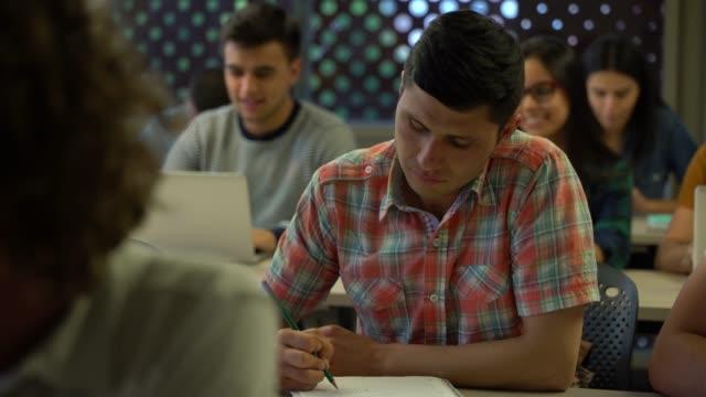 非常に焦点を探してノートにメモを取ってラテン アメリカ男子生徒 - ノート点の映像素材/bロール
