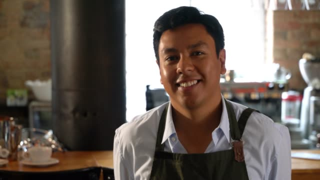 Latin American male waitress wearing his uniform while facing camera smiling at the restaurant
