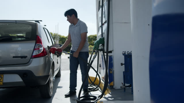 latin american man at a self service gas station refueling his tank - fuel pump stock videos & royalty-free footage