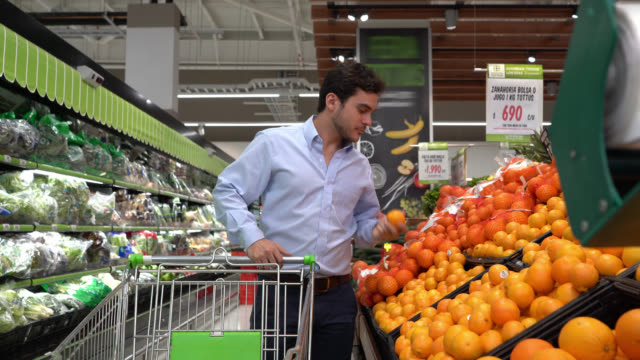 latin american man choosing oranges from fruit display at a supermarket while pushing cart - choosing stock videos & royalty-free footage