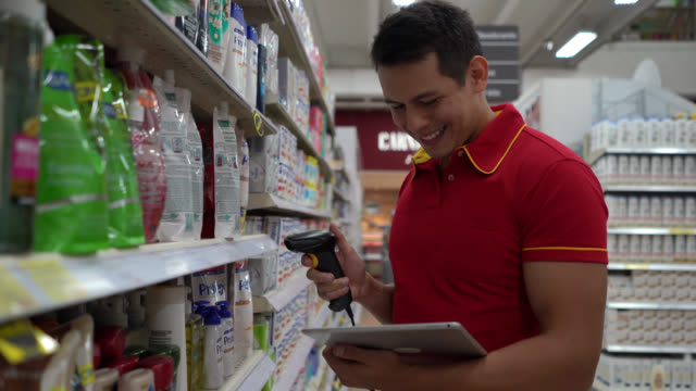 latin american man doing inventory at the supermarket with a bar code scanner and tablet smiling - assistant stock videos & royalty-free footage