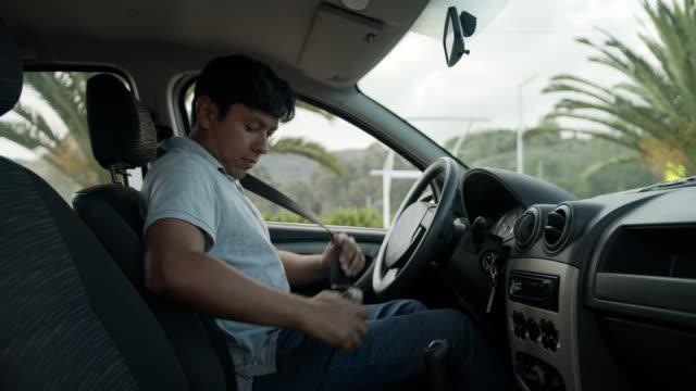 vídeos de stock e filmes b-roll de latin american man getting in his car fastening his seat belt - latin american and hispanic ethnicity
