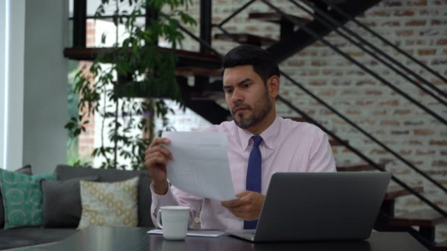 Latin american man looking at bills and paying them online with laptop while enjoying a coffee at home