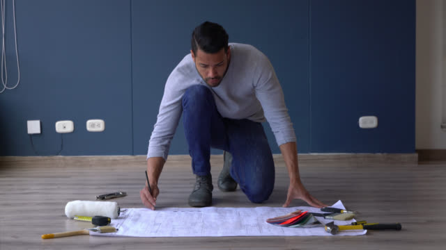 latin american man making plans while looking at a blueprint of his new home - color swatch stock videos & royalty-free footage