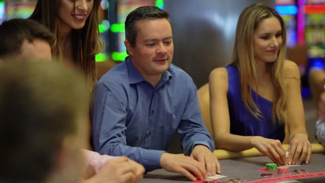 latin american man playing blackjack at the casino looking happy - blackjack stock videos and b-roll footage