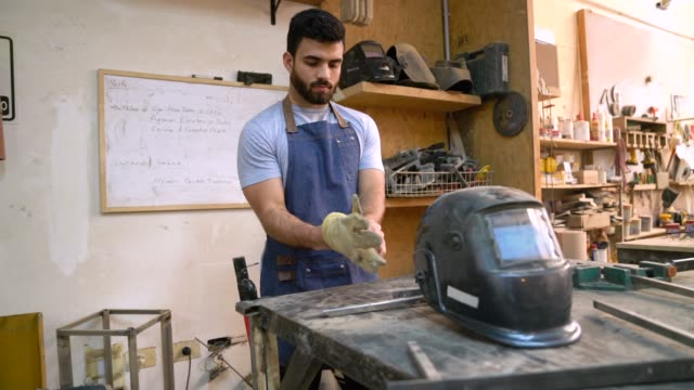 latin american man putting on all the protective wear before welding something - work helmet stock videos & royalty-free footage