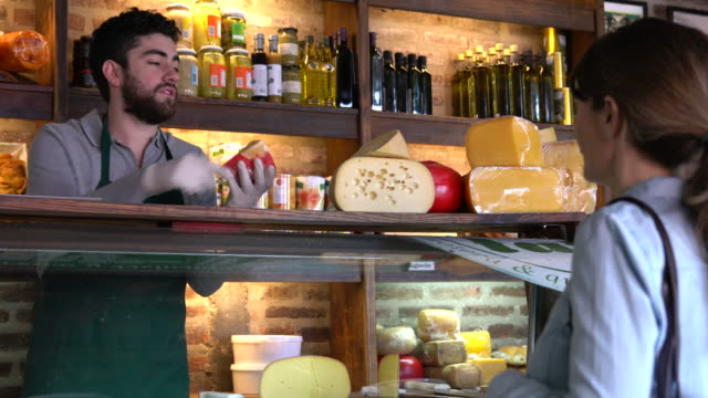 latin american man working at a delicatessen suggesting a type of cheese to female customer - grocer stock videos & royalty-free footage