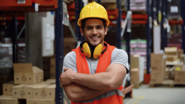 latin american man working at distribution warehouse looking at camera smiling with arms crossed - world trade organisation stock videos & royalty-free footage