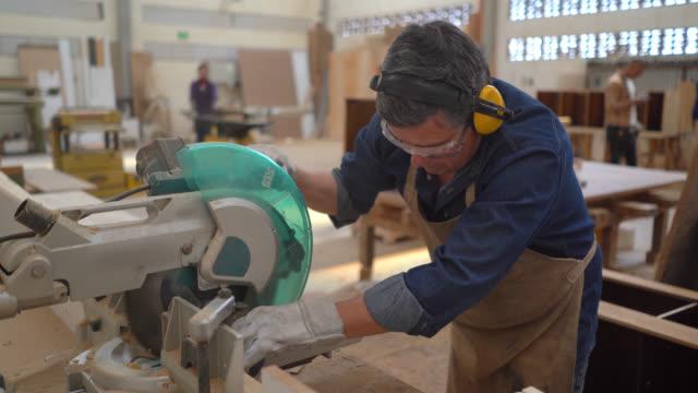 vídeos de stock e filmes b-roll de latin american man working at the carpentry cutting wood with a circular saw machine - protetor de ouvido