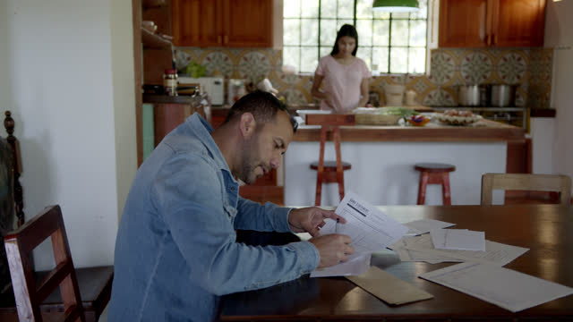 latin american man working with some documents while wife cooks dinner at a rural home - colombia stock videos & royalty-free footage