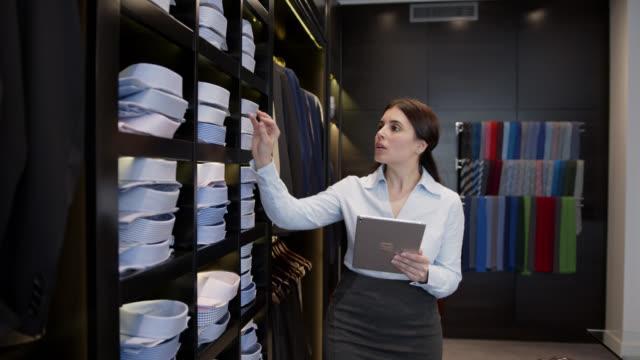 stockvideo's en b-roll-footage met latijns-amerikaanse manager van een formele kleding van een mens die inventaris doet gebruikend een tablet - kledingwinkel