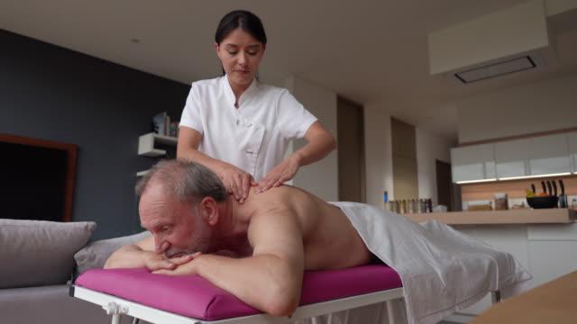 lateinamerikanische masseurin gibt eine entspannende massage zu einem senior-kunde zu hause - hausbesuch stock-videos und b-roll-filmmaterial