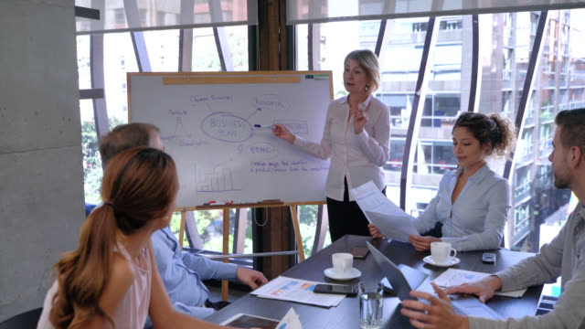 latin american mature business female manager explaining the strategic plan to her team using a white board - business strategy stock videos & royalty-free footage