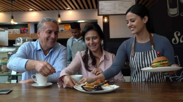 latin american mature couple at a restaurant drinking coffee and friendly waitress bringing their order - serving staff stock videos & royalty-free footage