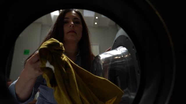 latin american mature female at a self service laundry loading the washing machine - tumble dryer stock videos & royalty-free footage
